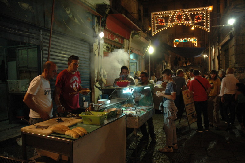 A night-time food market in the Vucciria district.  A small Piazza, a block from Via Roma.