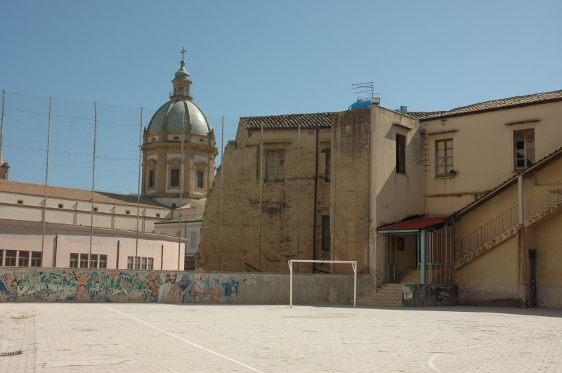 This open space belongs to the Oratorio Salesiano S. Chiara, and the church of Il Gesu is behind.   The oratory is a multi-religious and multi-ethnic youth centre.  The setting suggests football or perhaps something more dramatic, tragic or sacred.